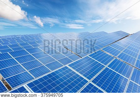 Close Up Top View Of Solar Energy Panels With Blue Sky With Couds Background. Clean And Renewable En
