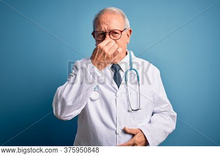 Senior grey haired doctor man wearing stethoscope and medical coat over blue background smelling something stinky and disgusting, intolerable smell, holding breath with fingers on nose. Bad smell