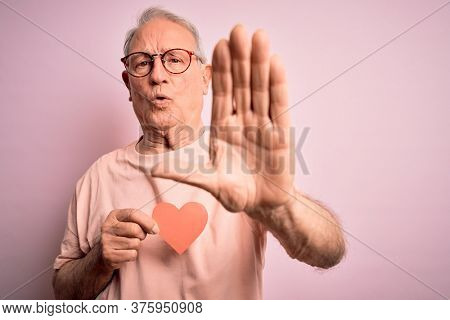 Senior grey haired man holding heart shape paper over pink background with open hand doing stop sign with serious and confident expression, defense gesture