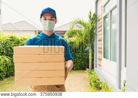 Asian Young Delivery Man Courier Sending And Holding Fast Food Pizza Boxed In Uniform He Protective