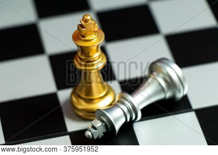 Top View Of Gold King Chess Piece Win Over Lying Down Silver King On Chess Board Background
