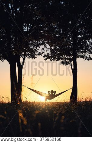 People On Vacation. A Girl's Silhouette In A Hammock Between Trees. A Hammock In The Background Of T