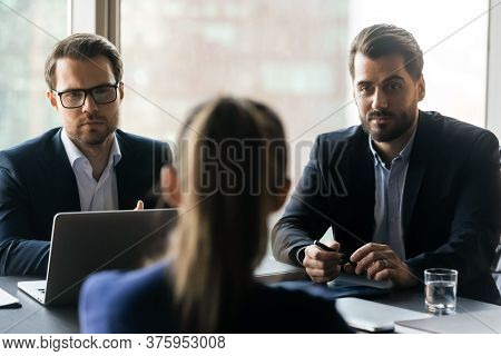 Serious Male Employers Listening To Female Job Seeker At Interview.