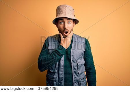 Handsome tourist man with beard on vacation wearing explorer hat over yellow background Looking fascinated with disbelief, surprise and amazed expression with hands on chin