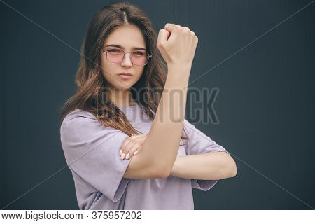 Young Stylish Trendy Woman Isolated Over Grey Blue Background. Serious Strong Powerful Girl Showing
