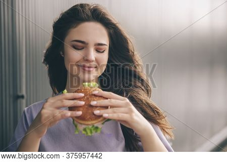 Young Stylish Trendy Woman Isolated Over Grey Blue Background. Happy Positive Girl Looking At Tasty