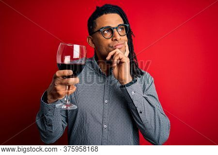 Young african american afro sommelier man with dreadlocks drinking glass of wine serious face thinking about question, very confused idea