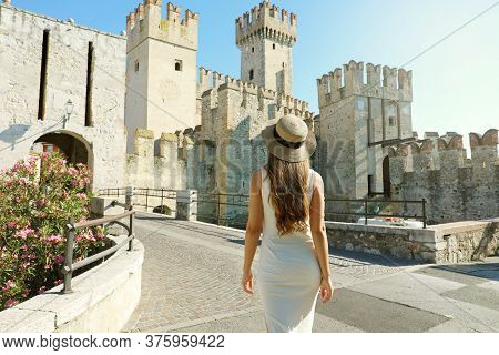 Travel In Italy. Back View Of Tourist Woman Walking In Sirmione Towards The Scaligero Castle. Rear V