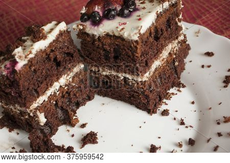 The Last Two Pieces Of Chocolate Sponge Cake With Cream On A White Plate Is Decorated With Multicolo