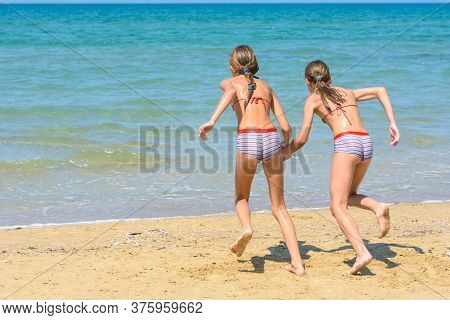 Children With A Run Run Swimming In The Sea