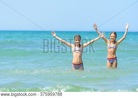 Children Stand In Sea Water And Joyfully Raise Their Hands Up