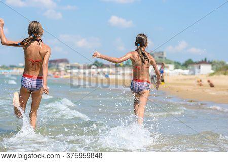 Two Girls Joyfully Run Along The Sea On A Warm Summer Day, Rear View