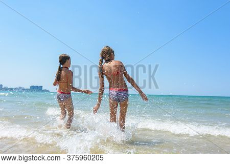 Two Girls Went Knee-deep Into The Water And Enjoy The Sea