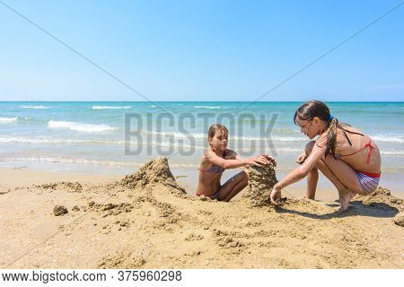 Two Girls Play In The Sand On The Beach Of The Sea Coast