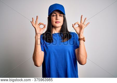 Young delivery woman with blue eyes wearing cap standing over blue background relax and smiling with eyes closed doing meditation gesture with fingers. Yoga concept.