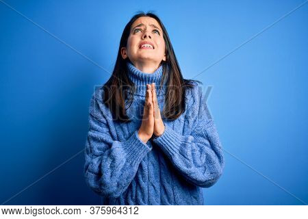 Young brunette woman with blue eyes wearing casual turtleneck sweater begging and praying with hands together with hope expression on face very emotional and worried. Begging.