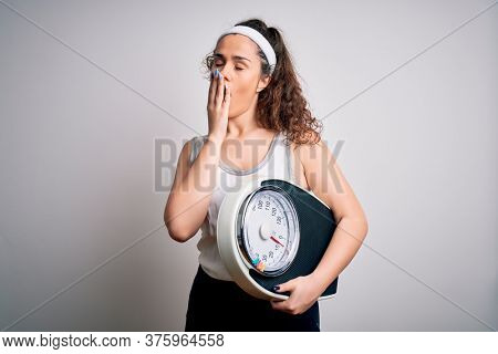 Young beautiful woman with curly hair holding weighing machine over white background bored yawning tired covering mouth with hand. Restless and sleepiness.