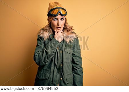 Middle age beautiful blonde skier woman wearing snow sportwear and ski goggles Looking fascinated with disbelief, surprise and amazed expression with hands on chin
