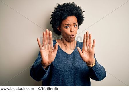 Young beautiful African American afro woman with curly hair wearing casual sweater Moving away hands palms showing refusal and denial with afraid and disgusting expression. Stop and forbidden.