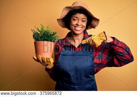Young African American farmer woman with curly hair wearing apron holding pot with plants with surprise face pointing finger to himself