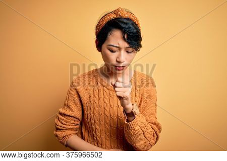 Young beautiful asian girl wearing casual sweater and diadem standing over yellow background feeling unwell and coughing as symptom for cold or bronchitis. Health care concept.