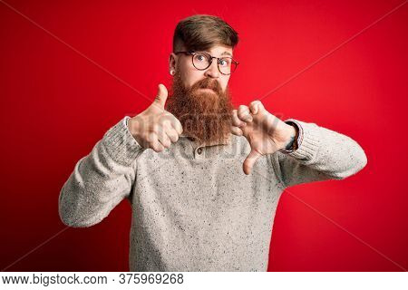 Handsome Irish redhead man with beard wearing casual sweater and glasses over red background Doing thumbs up and down, disagreement and agreement expression. Crazy conflict