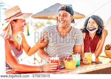 Friends Trio Drinking At Beach Cocktail Bar Wearing Face Masks - New Normal Summer Concept With Guy