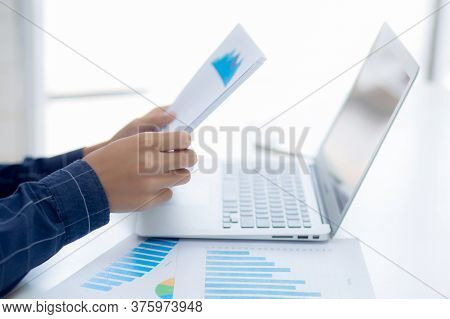 Hand Of Young Business Man Looking Document Data Graph And Chart Paper, Marketing And Investment, Re