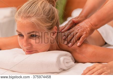 Blonde Woman Lying Down And Enjoying A Massage Given By Two Hands . Well-being And Leisure Concept.