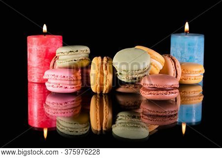 An Assortment Of Sweet Macaroons With Two Lit Candles In The Back On A Reflective Surface