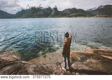 Man Walking On Beach Solo Travel Vacation In Norway Outdoor Traveler Enjoying Fjord And Mountains Vi