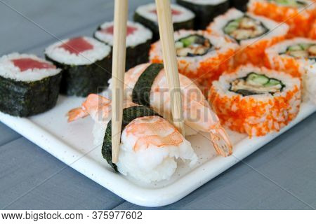 Fresh Sushi Set Maki And Rolls On Wooden Table. Close-up Of Chopsticks Holding Nigiri With Shrimps