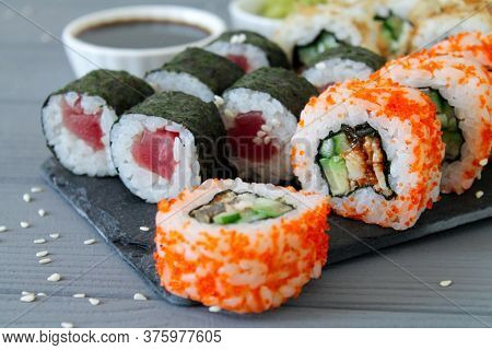 Close-up Of Sushi Set California And Maki Rolls On Stone Board