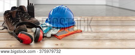 Work Safety Protection Equipment. Industrial Protective Gear On Wooden Table, Blur Site Background.
