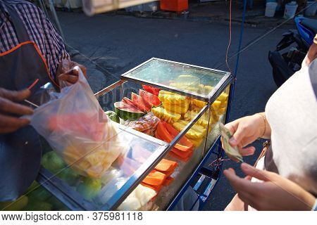 Tropical Fruit Street Vendor On The Streets Of Bangkok In Thailand, Slicing Different Fruits, A Woma