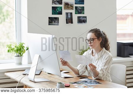 Portrait Of Modern Young Woman Holding Photographs Reviewing For Publishing While Working At Pc In W