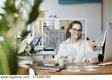 Portrait Of Creative Young Woman Smiling At Camera While Reviewing Photographs In Publishing Office,