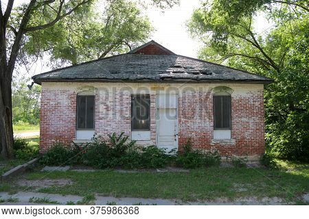 A Closed Boarded Overgrown Abandoned Rural Town Building