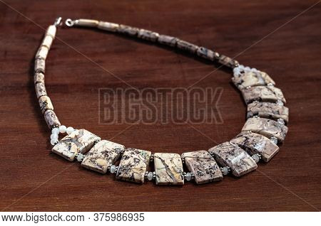Necklace Made Of Ural Jasper On Wooden Background