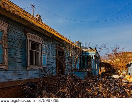 Semi-destroyed Wooden House In Russian Style With Piles Of Construction Debris Around
