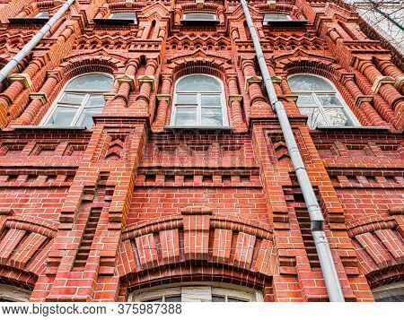 A Look From Below At The Red Brick Building With Tin Drainpipes