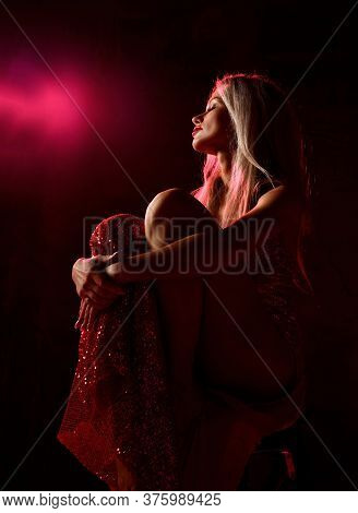 Young Beautiful Blonde Woman In Sexy Red Shiny Dress With Open Legs Sitting On Chair, Holding Tight