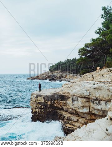 Man Standing At Edge Looking At Sea Windy Weather