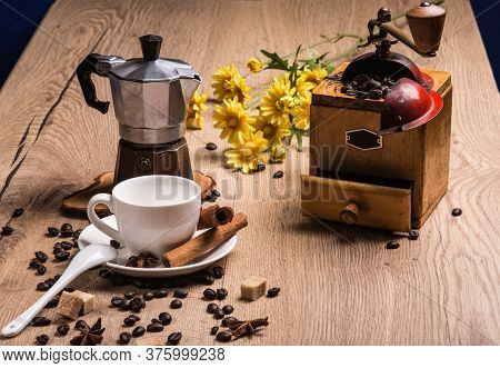On Table Is A Coffee Maker Mocha, Vintage Coffee Grinder. White Saucer With Cup Are Cinnamon Sticks
