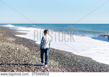 Young Baby Boy Walking Along Shoreline Of Beach