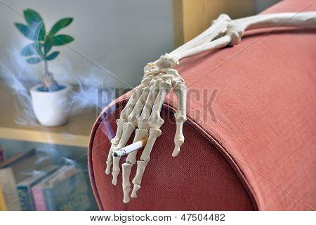 Cigarette in hand of skeleton