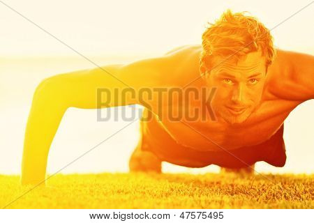 Sport fitness man push-ups. Male athlete exercising push up outside in sunny sunshine. Fit shirtless male fitness model in exercise outdoors. Healthy lifestyle concept.