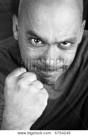 Angry man with shaved head making a fist poster
