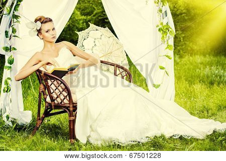 Charming elegant bride under the wedding arch. Wedding dress and accessories. Wedding decoration.