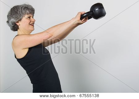 Middle Aged Female Sports Trainer Lifts Kettle Bell